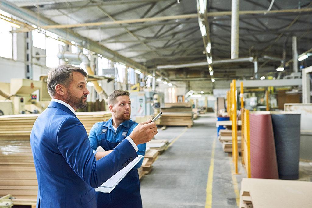 Un homme qui contrôle une entreprise accompagné d'un ouvrier de l'entreprise