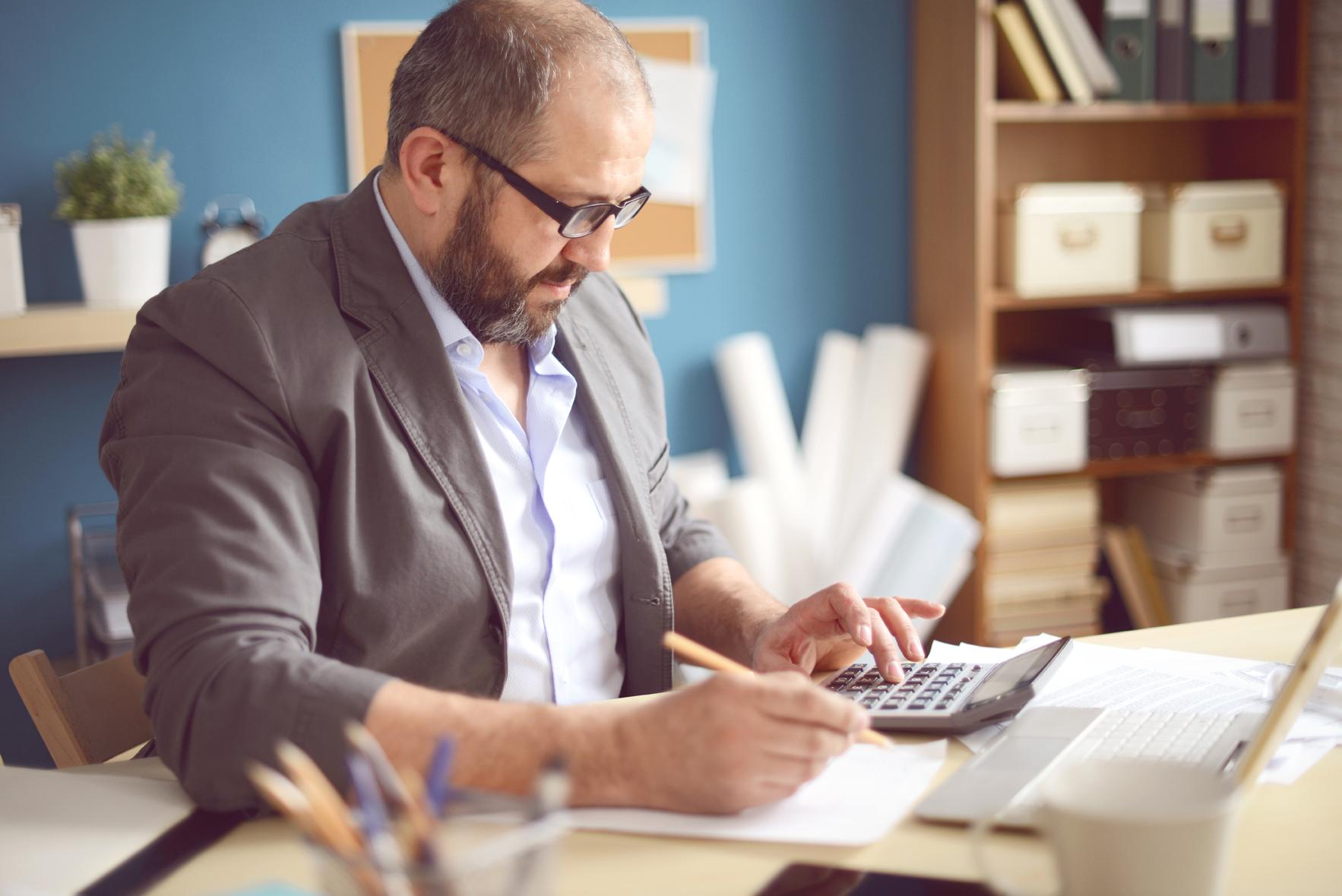 homme assis à son bureau qui fait des calculs