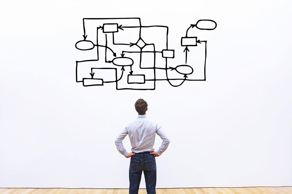 Homme face à un mur qui regarde un schéma très compliqué