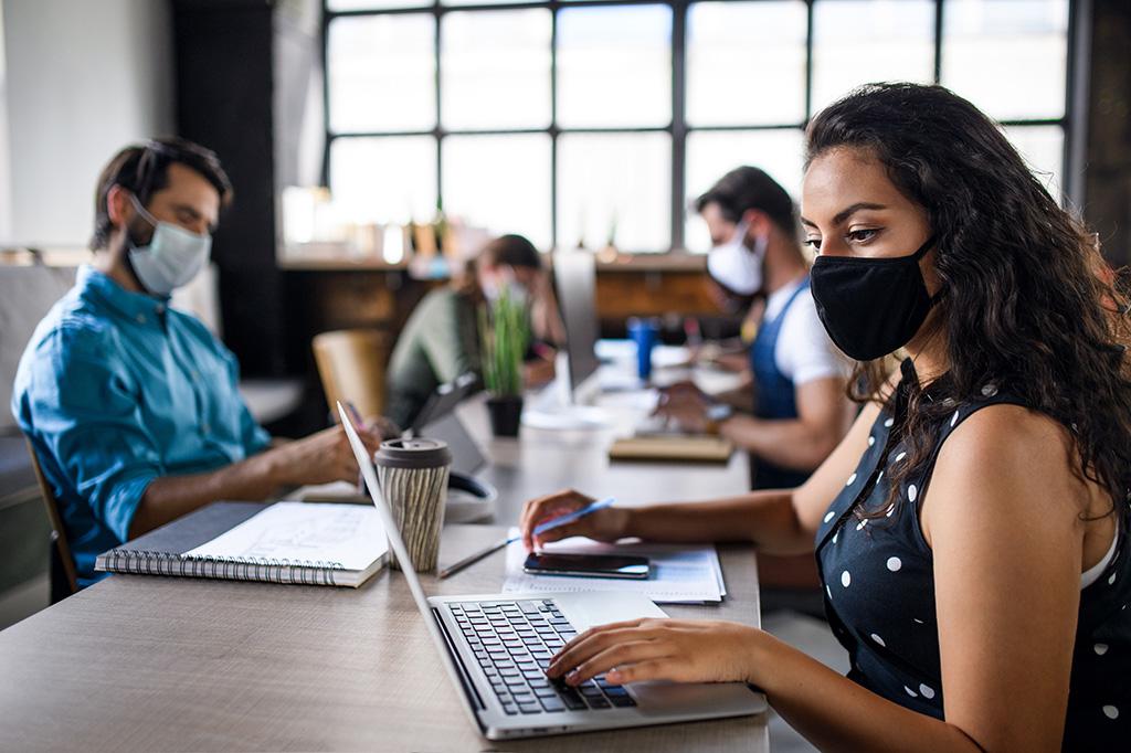 des employés qui travaillent avec distanciation sociale et masque